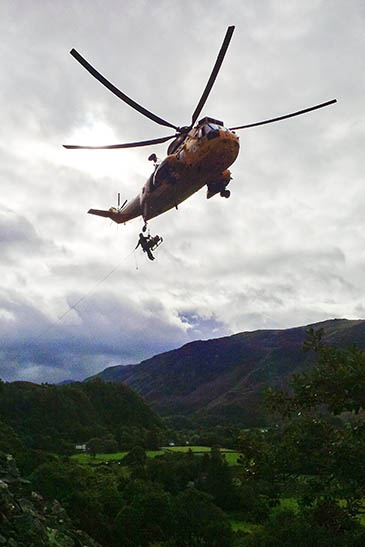 The injured climber is winched into the RAF Sea King at Shepherd's Crag. Photo: Peter Little/Keswick Mountain Rescue Team