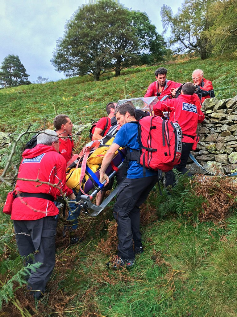 Rescuers stretcher the injured walker down from the fell. Photo: Keswick MRT