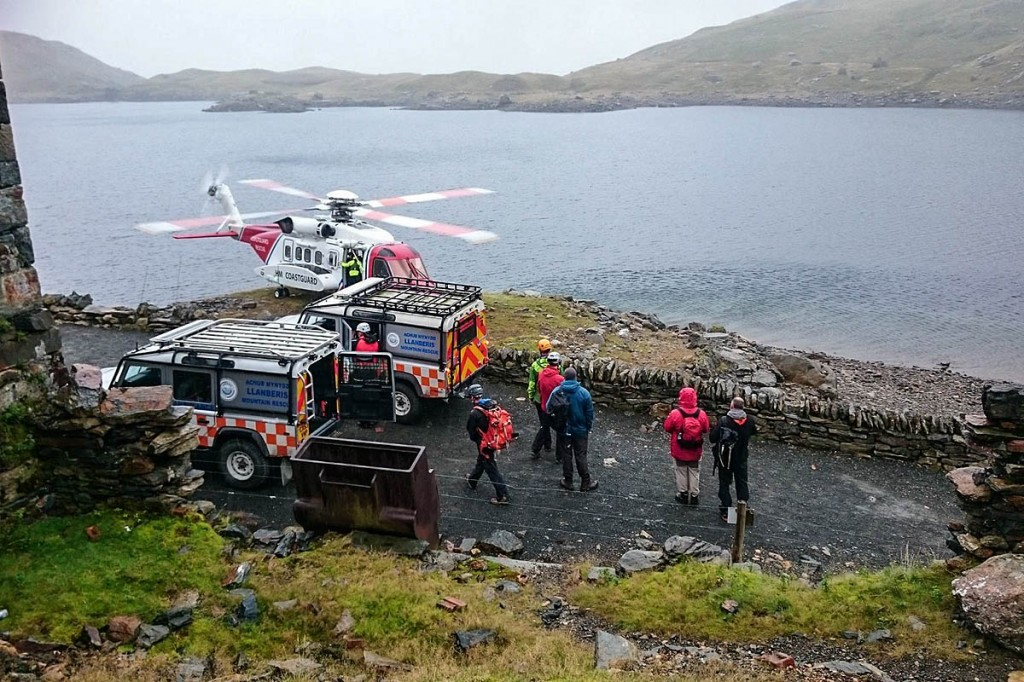 Rescue team members at the site, with the Caernarfon Coastguard helicopter. Photo: Elidir Owen/Miles Hill/Llanberis MRT