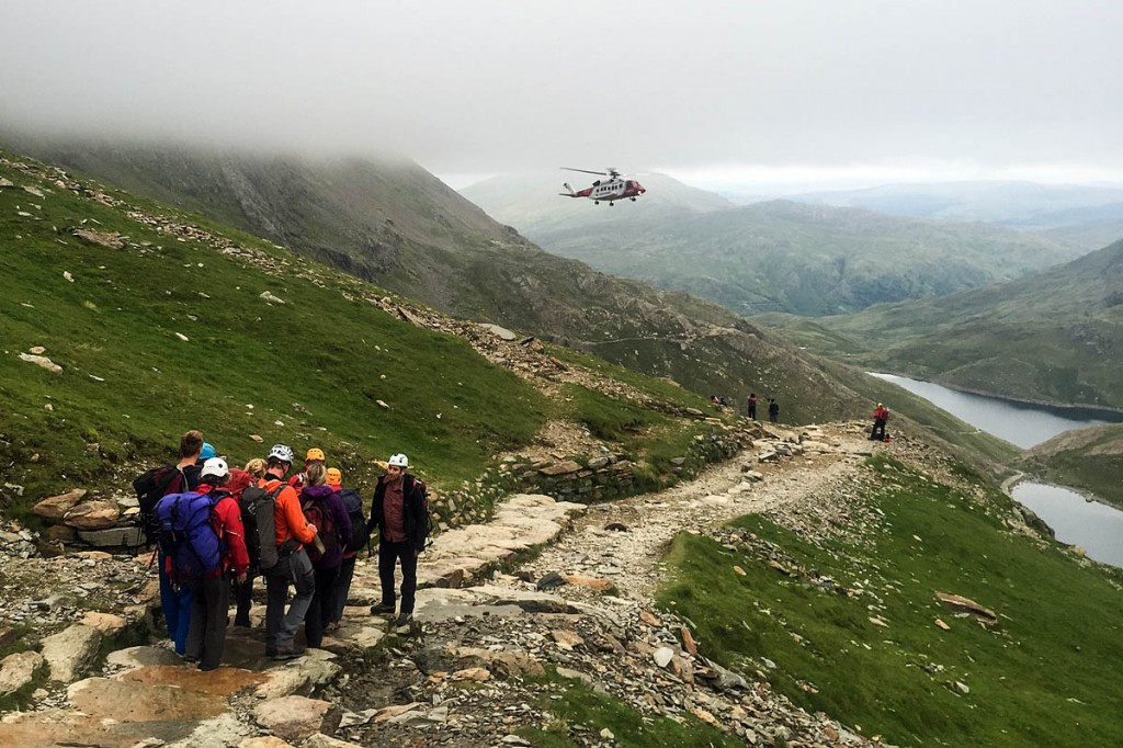 Members of the Llanberis team stretcher a casualty towards hovering Coastguard helicopter. Photo: Steve Nelson/Sarda Wales
