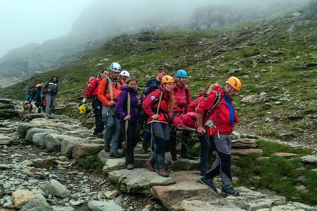 Members of LLMRT carry a stretcher on the Pyg Track on Snowdon. Photo: Rob Booth