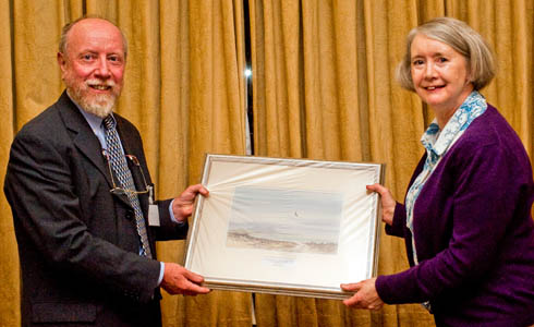 Marion Shoard receives her award from guild president Roly Smith. The award takes the form of an original painting of North Uist by guild member David Bellamy. Photo: Jon Sparks
