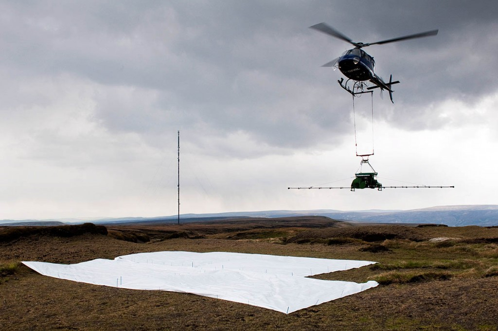 A helicopter drops moss on to the moors as part of the project