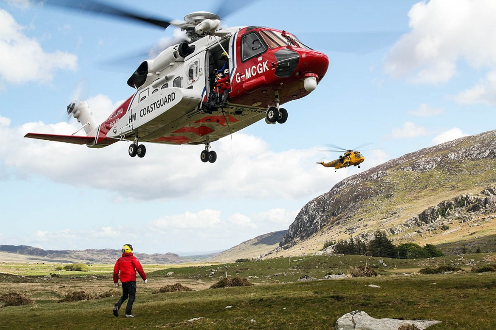 The RAF Sea King flies past as rescuers train with one of the new Sikorksky S-92s. Photo: John Hulse
