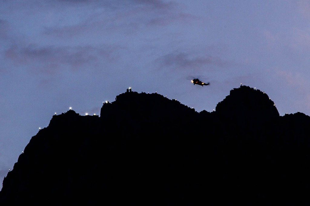 The RAF helicopter flies over the ridge as rescuers illuminate Tryfan