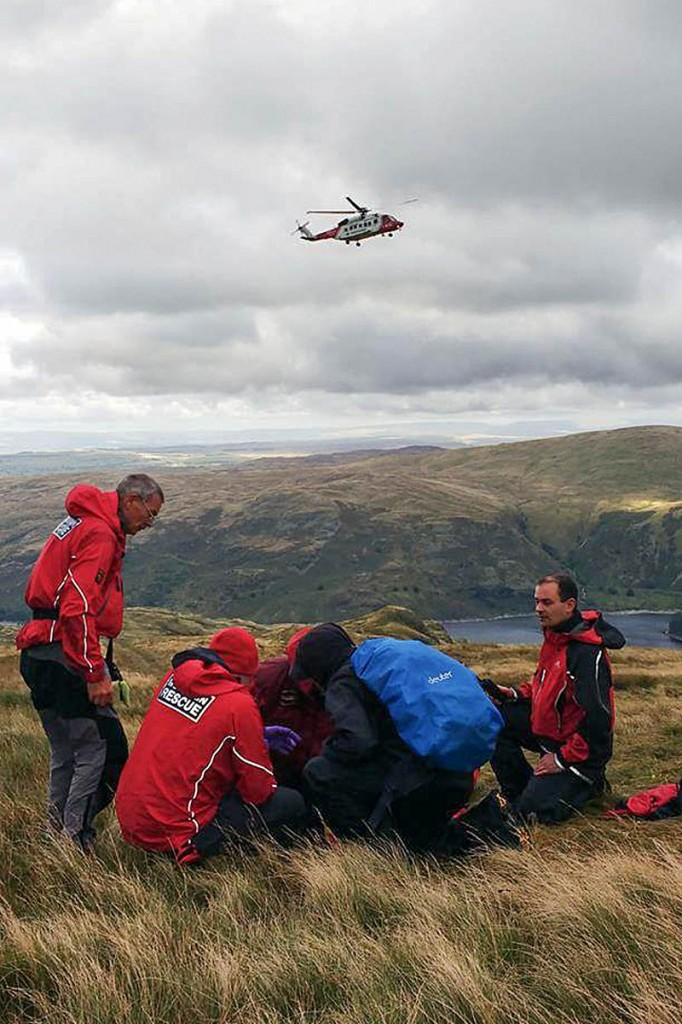 The Coastguard helicopter approaches as rescuers treat the injured man. Photo: Penrith MRT