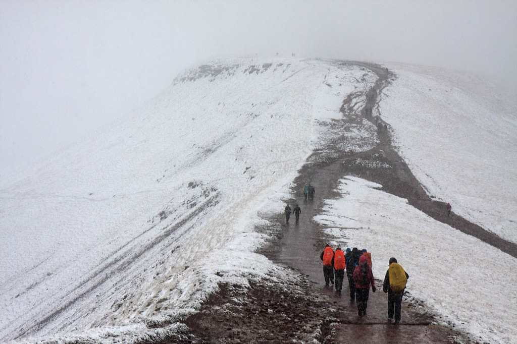 Walkers head towards south Wales's highest peak Pen y Fan in wintry conditions