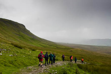 Rain approaches as walkers descend from Pen-y-ghent, one of Yorkshire's Three Peaks