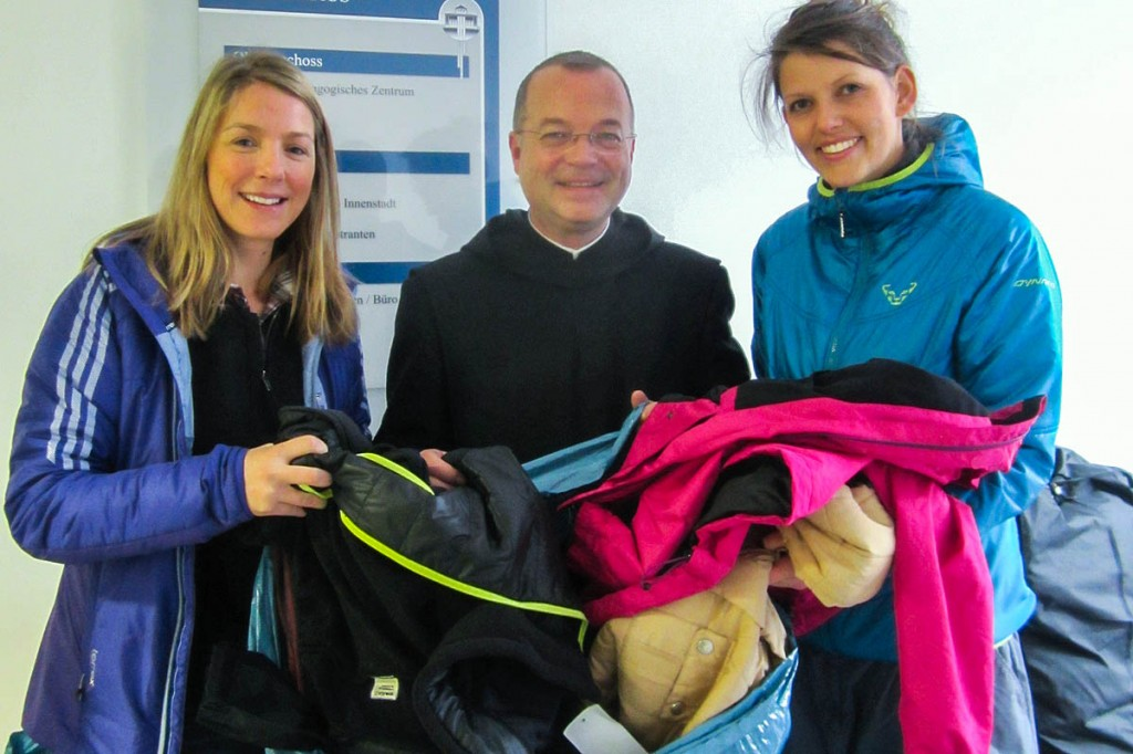 Irina Mock, PrimaLoft European PR manager, left, and Kathrin Pildner, the brand's trade marketing manager, hand over the jackets to Brother Emmanuel at the charity