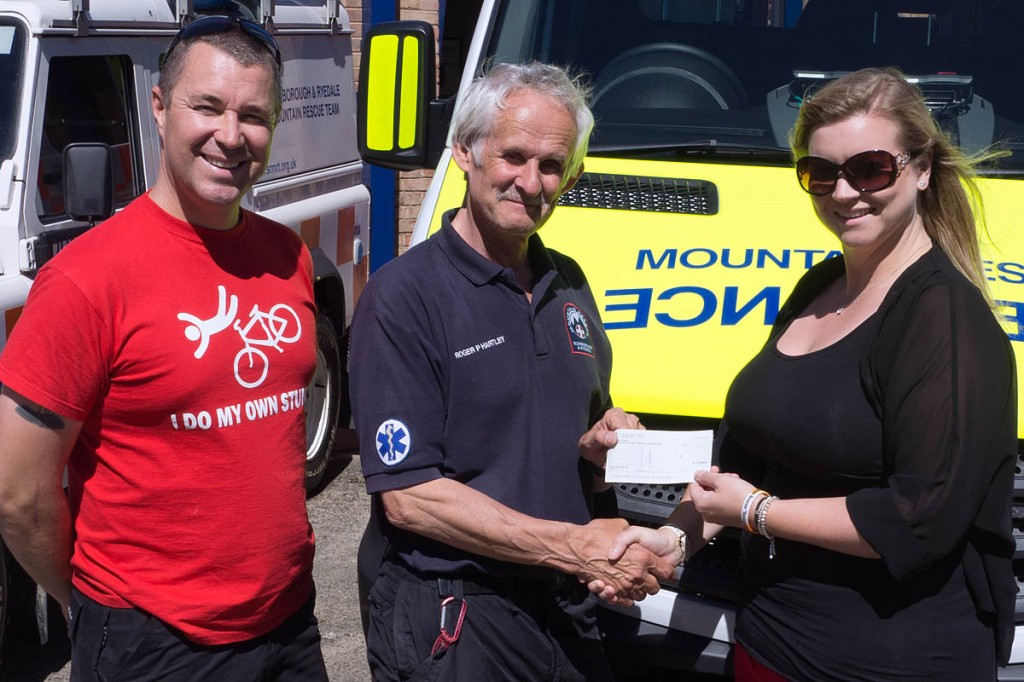 Neil and Becky Robinson present the cheque to Roger Hartley of the team