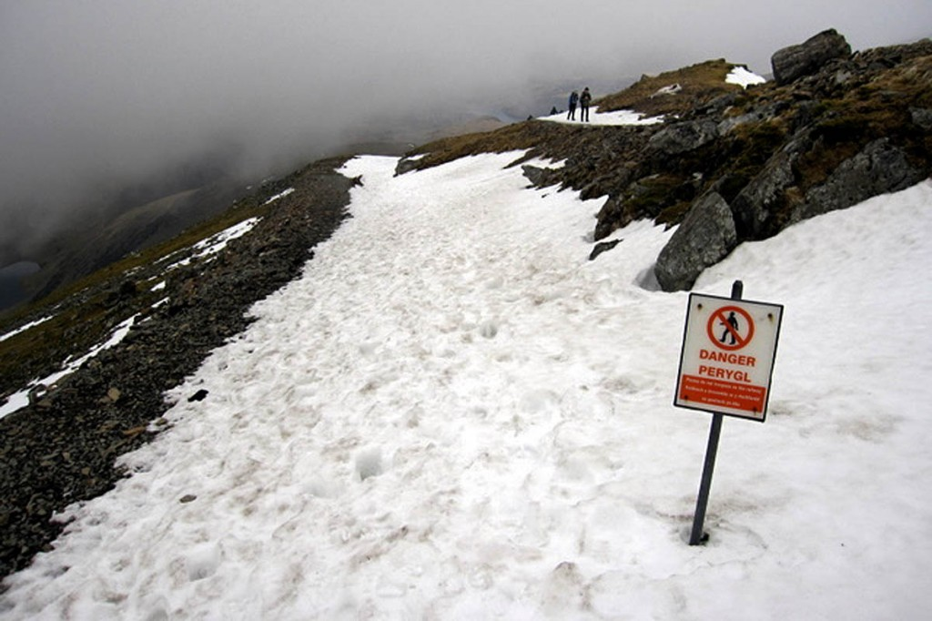 The Snowdon Mountain Railway is banked up with snow above big cliffs. Photo: John S Turner CC-BY-SA-2.0