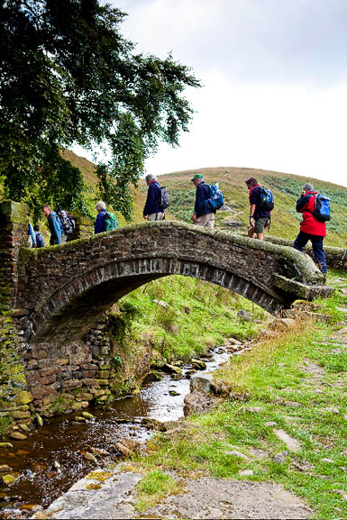 Walkers on a packhorse bridge in the South Pennines