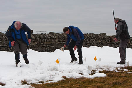 The surveyors pinpoint the highest part of the hill, which is partly covered in snow
