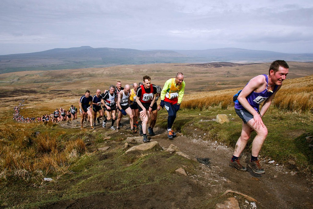 Runners ascend Pen-y-ghent in a previous race, with Ingleborough and Whernside in the distance
