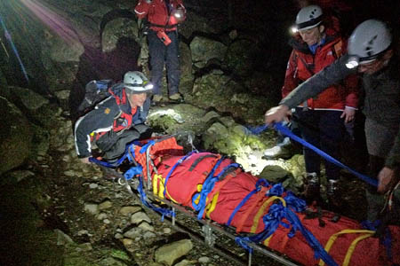Rescuers prepare to stretcher the walker off the mountain