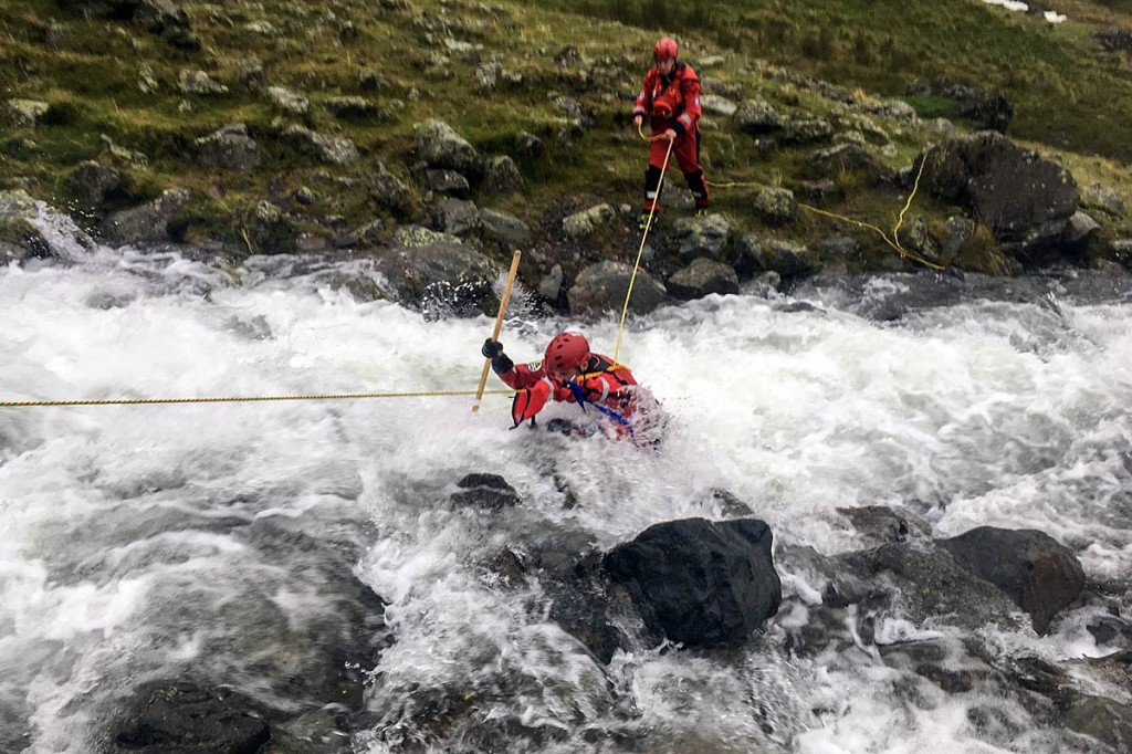 Swiftwater technicians from the Wasdale team cross the swollen beck in Lingmell Gill on Saturday. Photo: Wasdale MRT