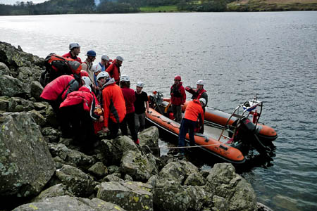 Rescuers prepare to put the walker into their boat. Photo: Wasdale MRT