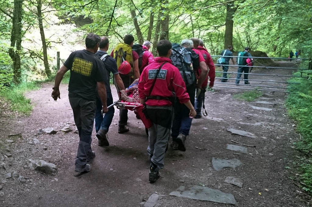 Rescuers carry the man from the site. Photo: Western Beacons MSRT