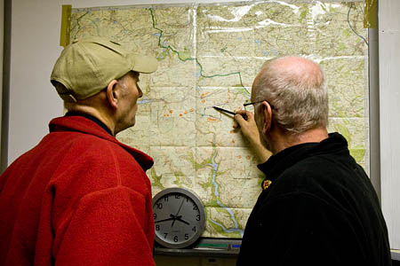 Dog handler Ken Sloan, left, and search manager Mike France map out the night's plan