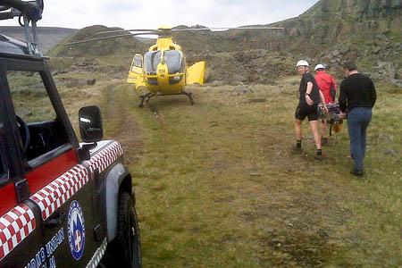 Rescuers carry the walker to the air ambulance